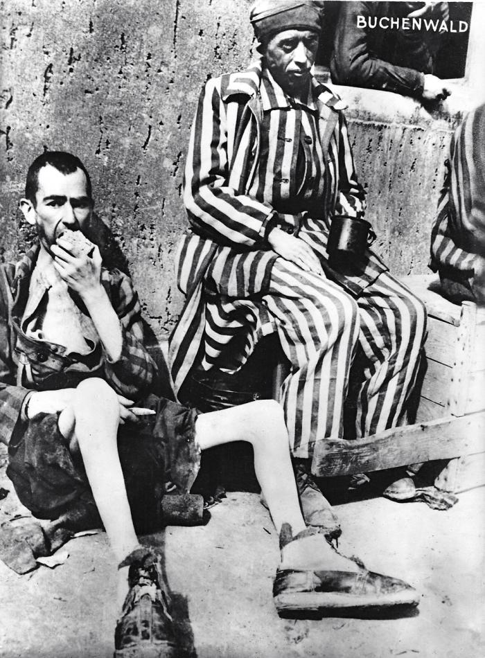 Photographie de deux déportés à la libération, un mangeant du pain © AFBDK